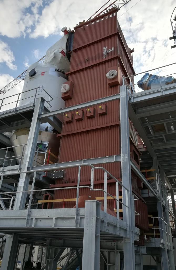 Vue de l'extérieur : la chaudière biomasse est installée verticalement, les petits tuyaux intégrés dans les parois contiennent de l'eau qui circule et se réchauffe au contact du foyer.